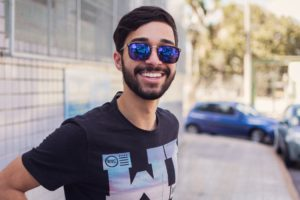 A guy with sunglasses on smiling